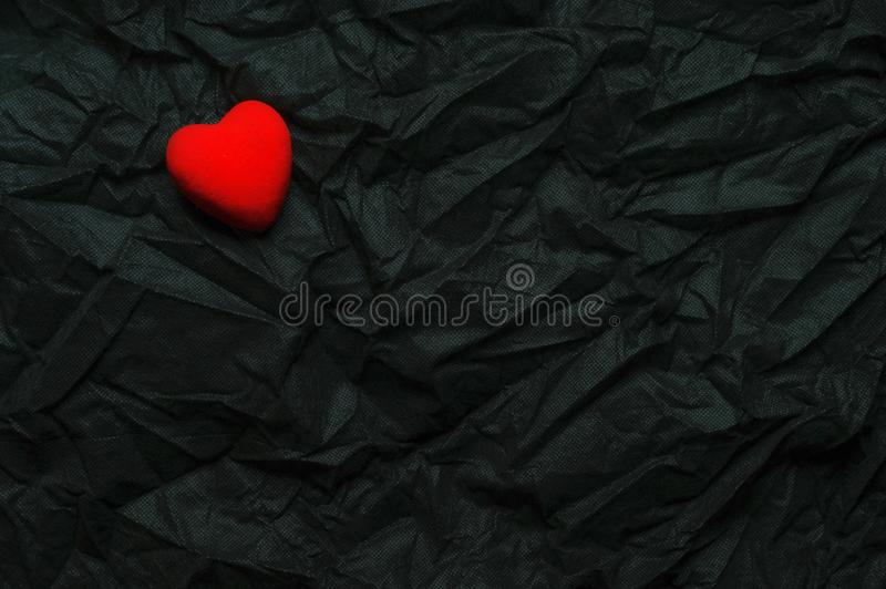 Top View Red Heart On Wrinkled Black Texture Background. Happy Valentine`s Day And Love Concept. Romantic Card, Banner Graphic royalty free stock photography