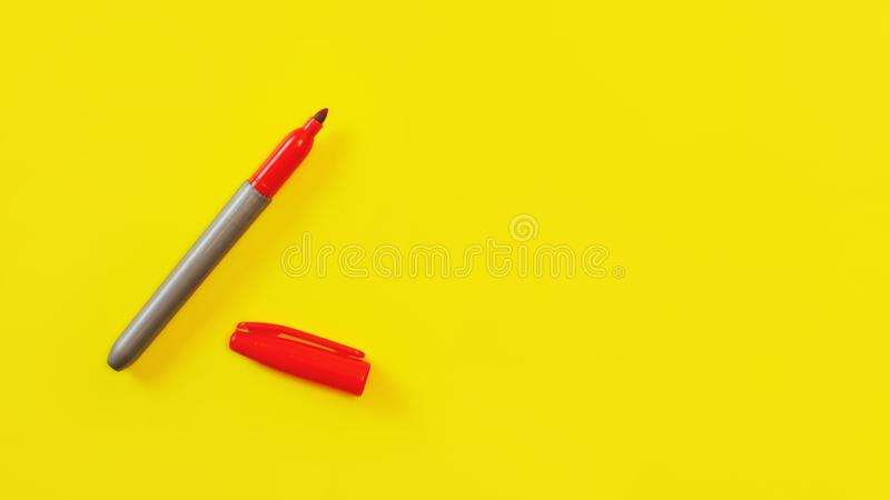 Top view on red marker, cap opened, on yellow board, copyspace for your text on right side stock photos