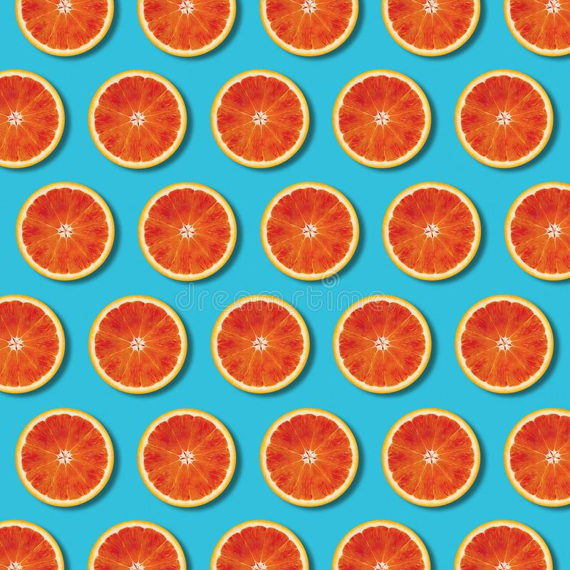 Top view red orange slices pattern on vibrant turquoise background stock image