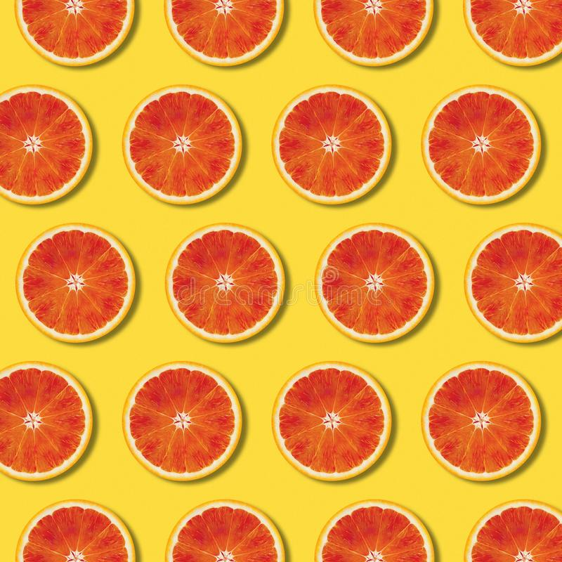 Top view red orange slices pattern on yellow background stock photos