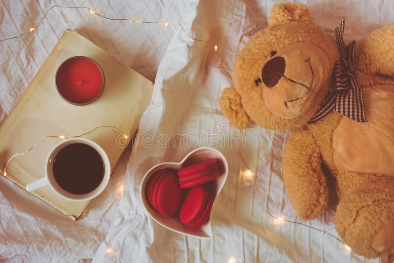 Top view of red or pink macarons in a heart shaped bowl, coffee, book, a candle and a teddy bear royalty free stock photo