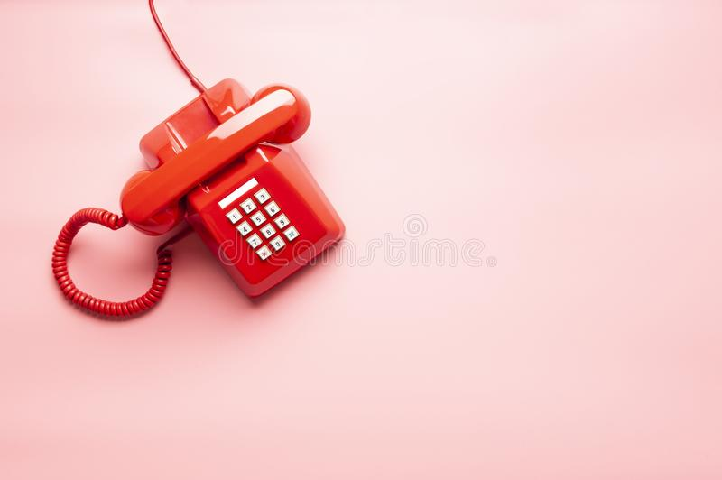 Red telephone on pink desk stock photography