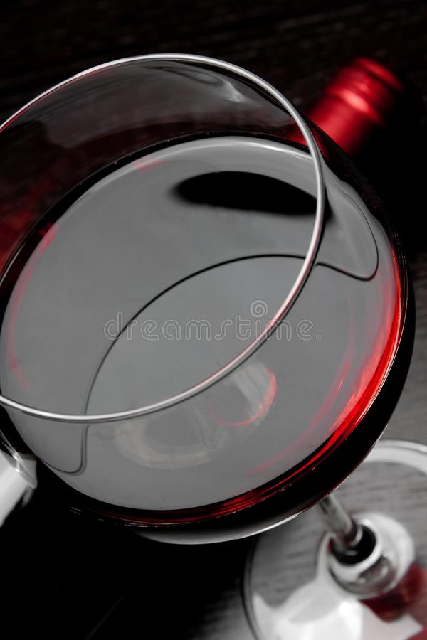 Top of view of red wine glass near bottle. On black wood table royalty free stock photography