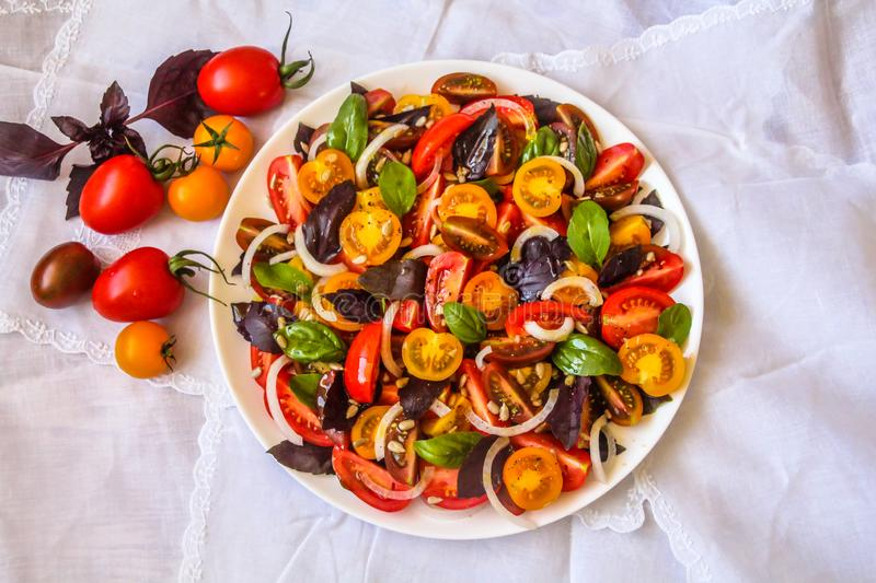 Top view of red & yellow cherry and plum tomato salad with basil leaves royalty free stock photography