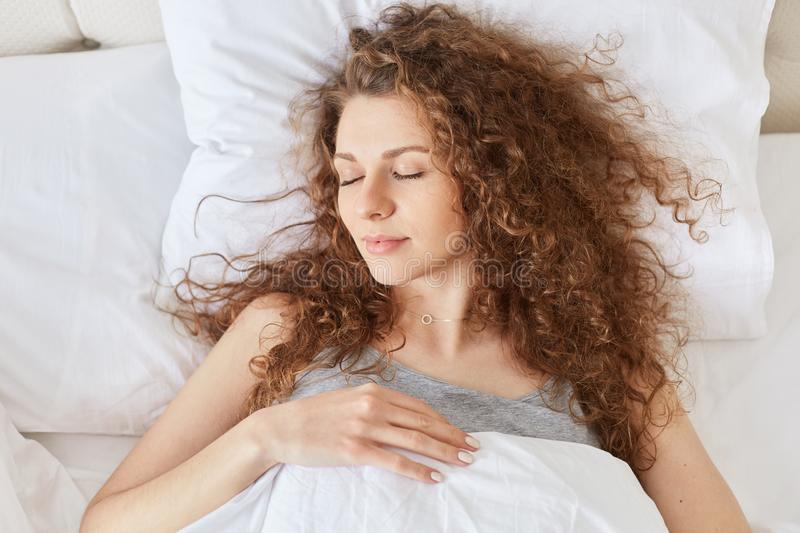 Top view of relaxed curly woman has healthy sleep in bed, lies on white linen, enjoys pleasant dreams at night, peaceful atmospher royalty free stock photo