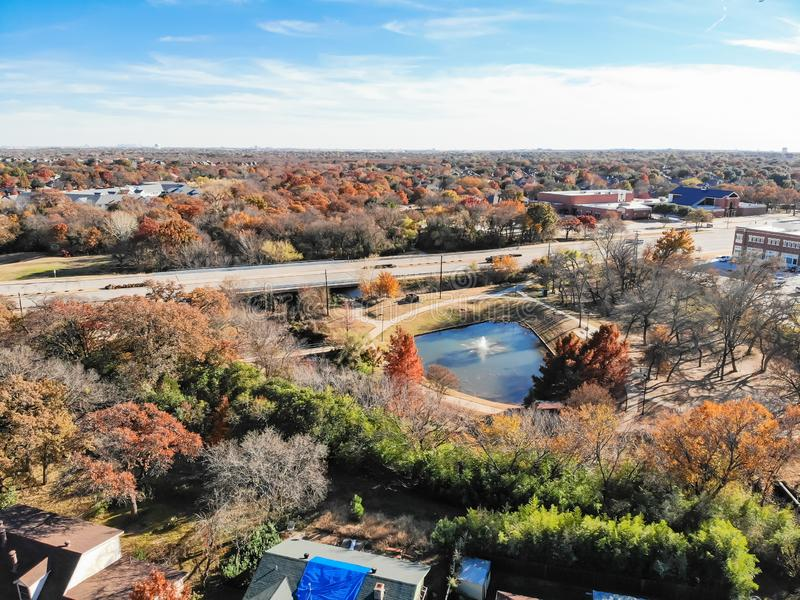 Top view residential area near pond and express way with colorful fall foliage. Aerial view lakeside neighborhood near highway with colorful autumn leaves in stock image
