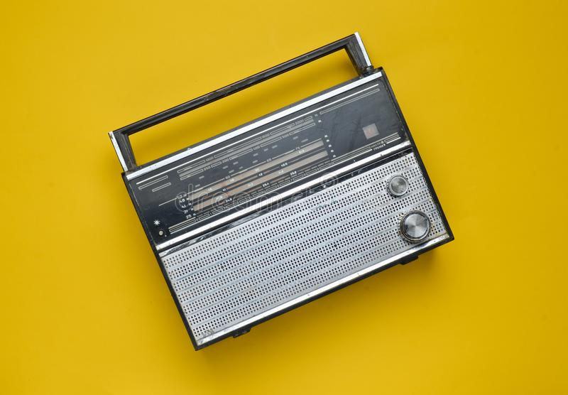Top view of a retro radio receiver on a yellow background. Culture of the 70s. stock photos