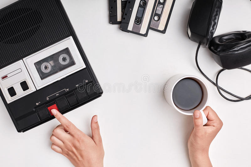 Top view of retro tape recorder, cassettes and headpnones lying on white surface. Woman`s hands switcing on old tape recorder list royalty free stock photos