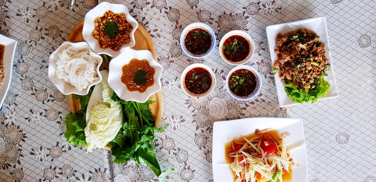 Top view of rice noodles with fresh vegetable and sweet sauce in wooden tray with spicy sauce. Papaya salad Thai style and Spicy minced pork on table for lunch royalty free stock image