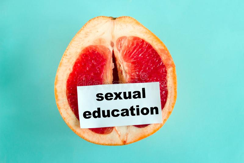 ripe juicy grapefruit with note sexual education isolated on a blue background stock images