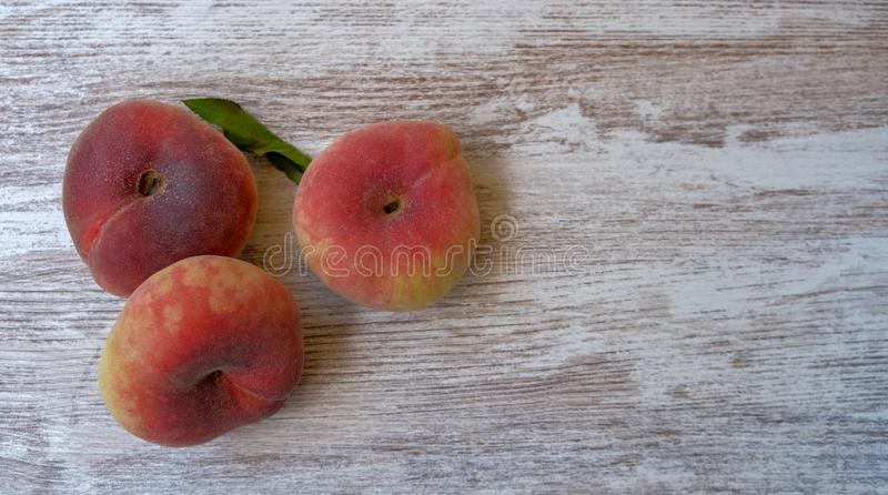 Top view on ripe juicy saturn peach on a wooden background stock photo