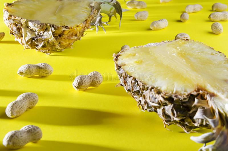 Close up of pineapple and peanuts in shell on colorful background.Shot with dark shadow. Top view of ripe pineapple in longitudinal section, unpeeled peanuts on royalty free stock images
