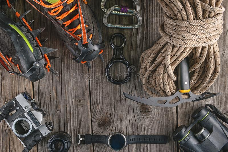 Top view of rock climbing equipment on wooden background. Chalk bag, rope, climbing shoes, belay/rappel device, carabiner and asce stock images