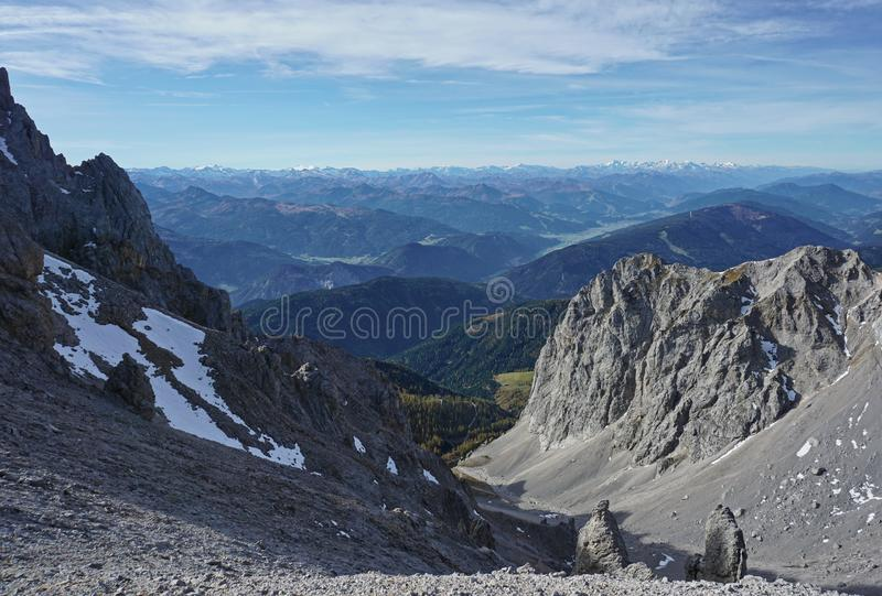 Top view from rocky mountains down to a green valley stock photo