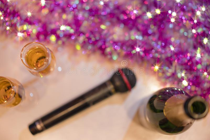 Top view of romantic couple of champagne flutes and bottle of sparkling wine with black karaoke microphone and pink garland. stock photo