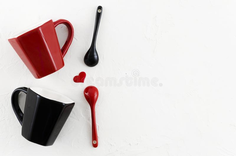 Top view romantic couple`s coffee mugs with heart, red and black ceramic spoons with copy space for your text or. Lettering royalty free stock photography