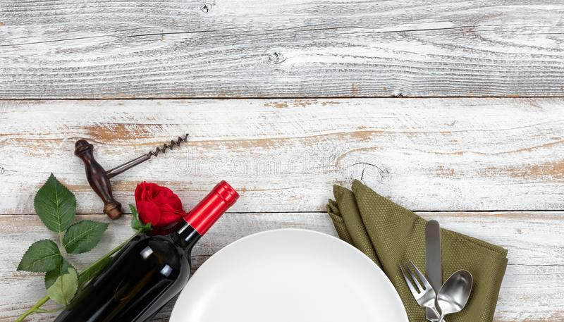 Top view of romantic dinner plate setting with red wine and rose stock photo
