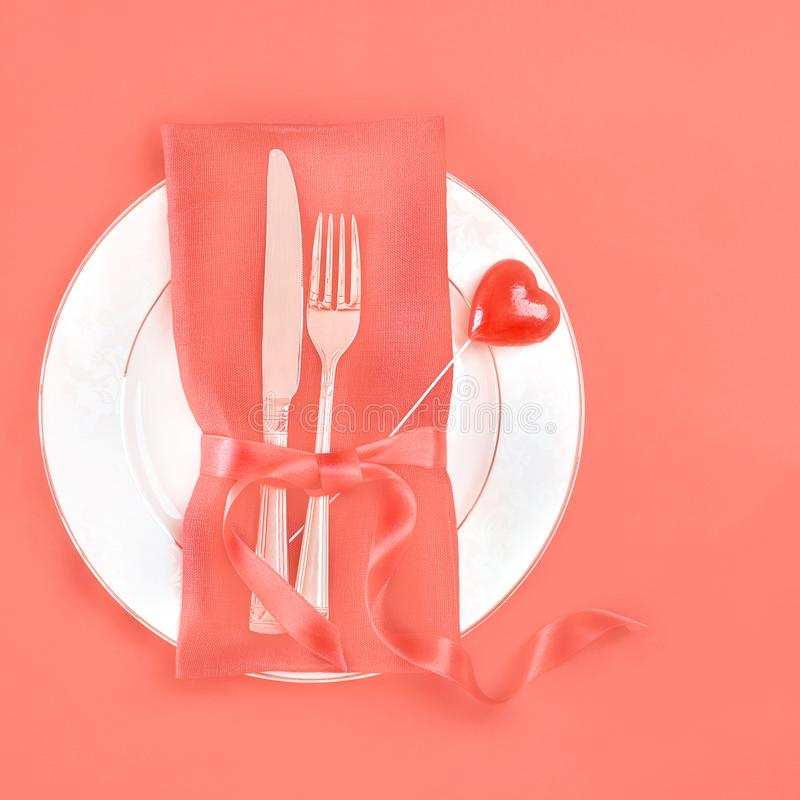 Top view romantic table setting for Valentines day or dinner date celebration wedding with red rose bud white plates fork and. Panton color of the year 2019 royalty free stock images