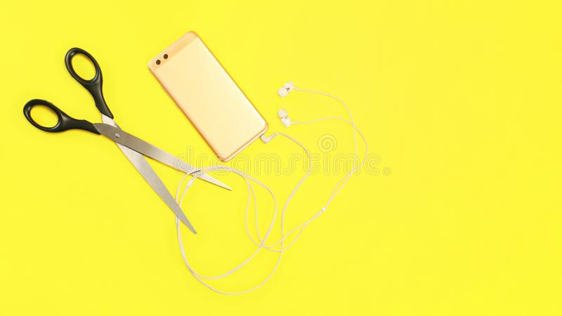 Top view on rose gold cell phone with ear buds cable to be cut with large scissors on yellow background royalty free stock photos