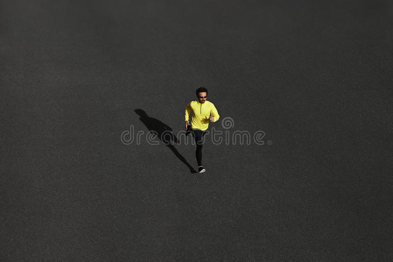 Top view runner man running sprinting for success on run at black road in yellow sportswear. Muscular fit sport model sprinter ex stock photo