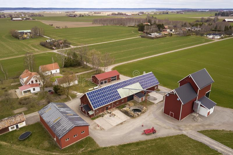 Top view of rural landscape on sunny spring day. Farm with solar photo voltaic panels system on wooden building, barn or house. Roof. Green field copy space royalty free stock photo