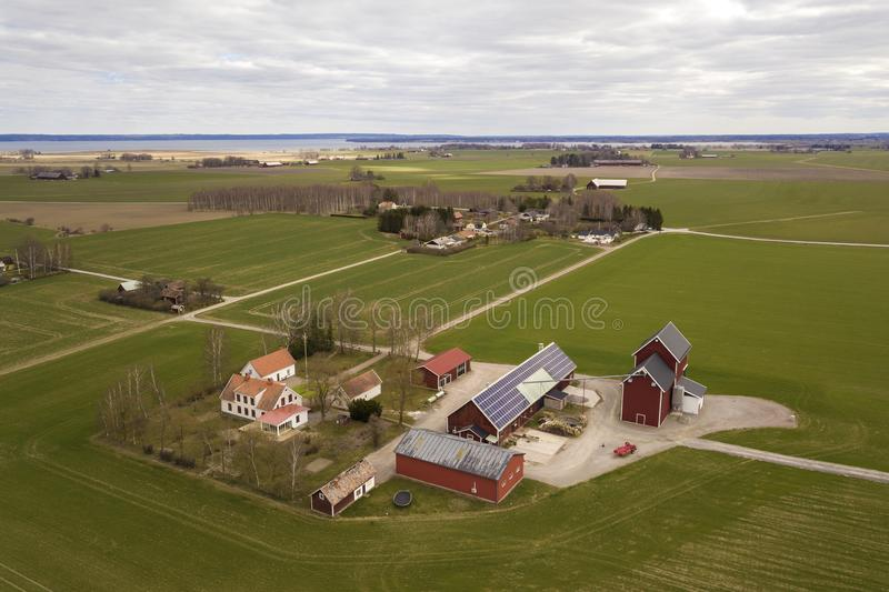Top view of rural landscape on sunny spring day. Farm with solar photo voltaic panels system on wooden building, barn or house. Roof. Green field copy space royalty free stock images