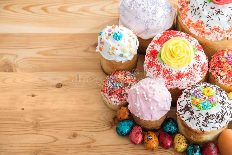 Top view Russian Easter cakes in glaze and decorations on wooden table with quail colored eggs royalty free stock photo