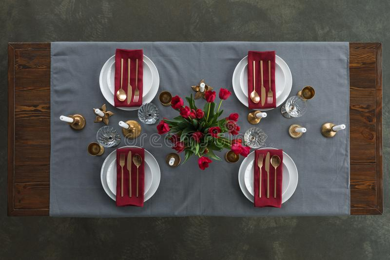 Top view of rustic table setting with red tulips bouquet, tarnished cutlery, wine glasses, candles and empty plates on tabletop stock photo