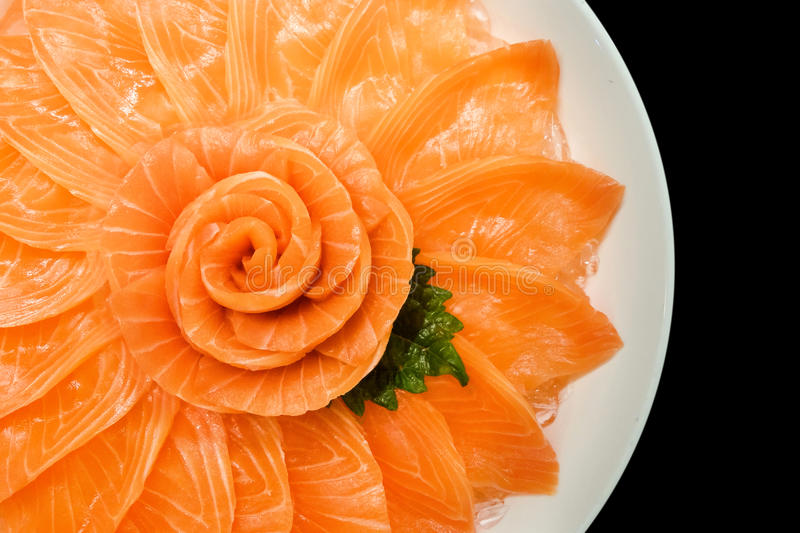 Top view of salmon sashimi serve on flower shape in white ice bowl boat isolated on black background, Japanese style. Top view closeup photo of Salmon sashimi stock photos