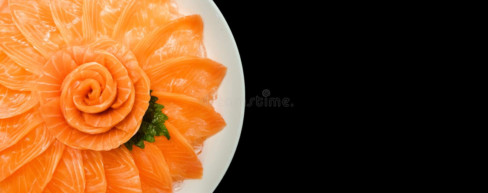 Top view of salmon sashimi serve on flower shape in white ice bowl boat isolated on black background, Japanese style stock photos
