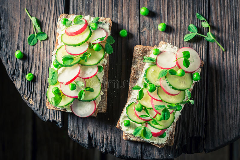 Top view of sandwich with fromage cheese, avocado and radish. On old wooden table stock photos