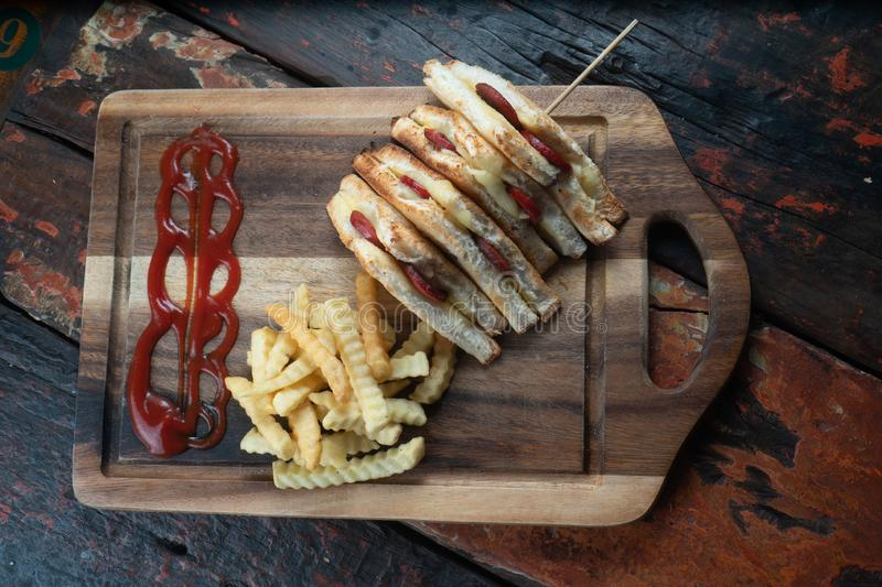 Sandwiches with Turkish sausage sucuk and cheese served aise with french fries on rustic wooden table. Top view of sandwiches with Turkish sausage sucuk and royalty free stock image