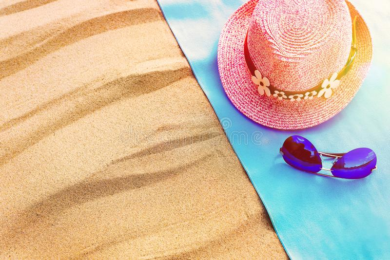 Top view of a sandy beach with a frame of blue towels with a hat and glasses. copy space and visible sand texture. royalty free stock photo