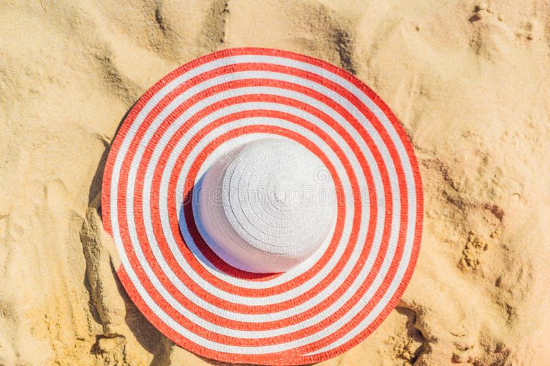 Top view of sandy beach with red striped beach hat Background with copy space and visible sand texture stock photography