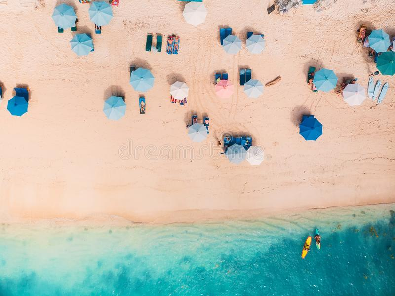 Top view of sandy beach with turquoise sea water and colorful blue umbrellas, aerial drone shot stock images
