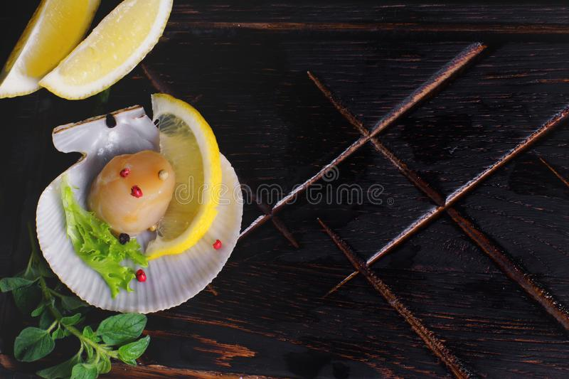 Top view on scallops fillet in its shell with spices and lemon royalty free stock photos