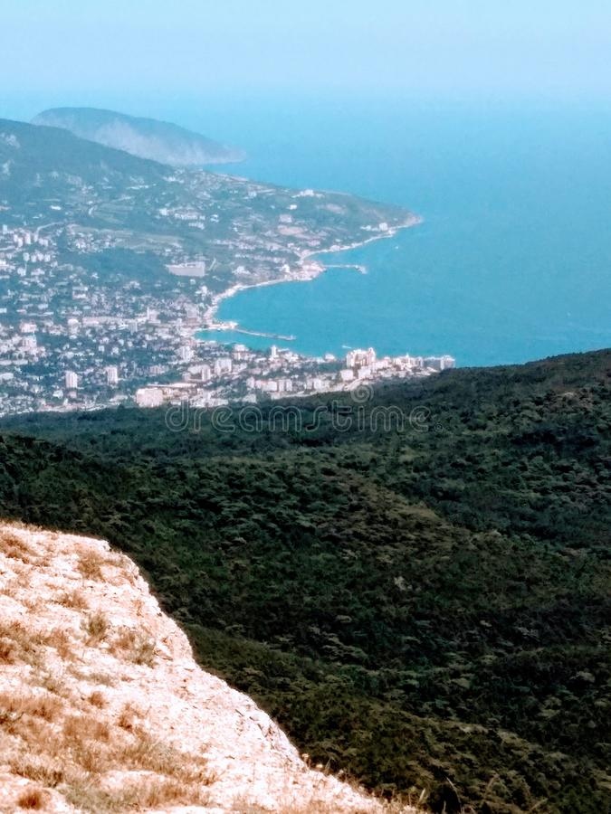 Top view of the sea coast, bay and coastal city in the sunshine, panorama from mountains covered with trees on a sunny summer day.  royalty free stock image