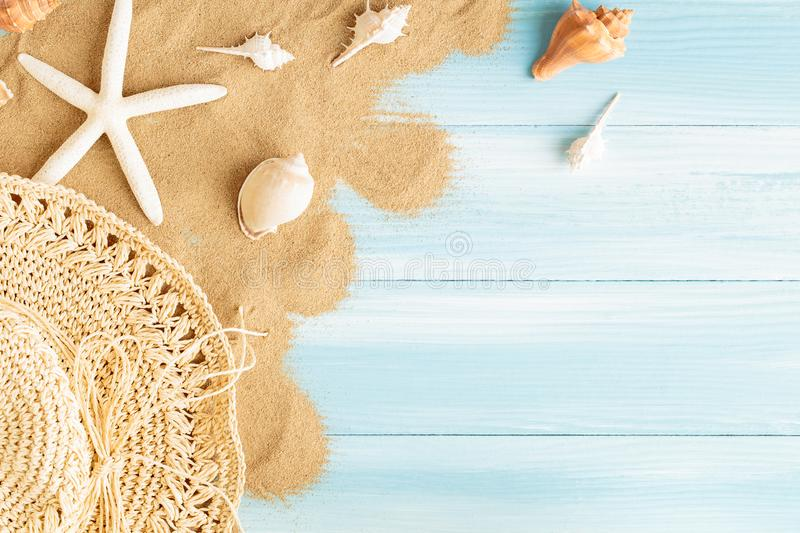 Top view of sea straw hat and sea shells on the sea sand on a blue wooden background, Summer concept on empty blue wood floor and royalty free stock images