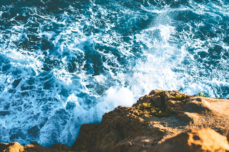 Top view of sea waves hitting rocks on the beach with turquoise blue sea water. rock cliff seascape in Atlantic ocean coastline. Splashing water in coast with royalty free stock photo