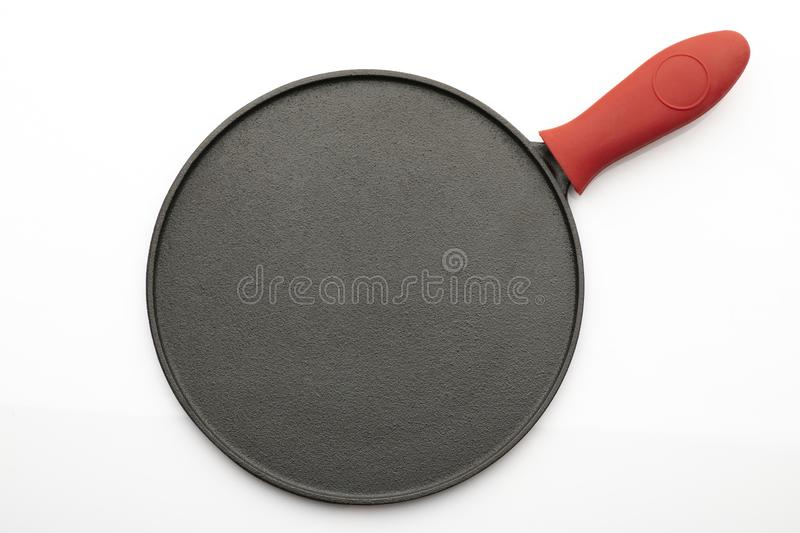 Top View of Seasoned Cast Iron Pan on White Background with Red Silicon Handle Grip stock image