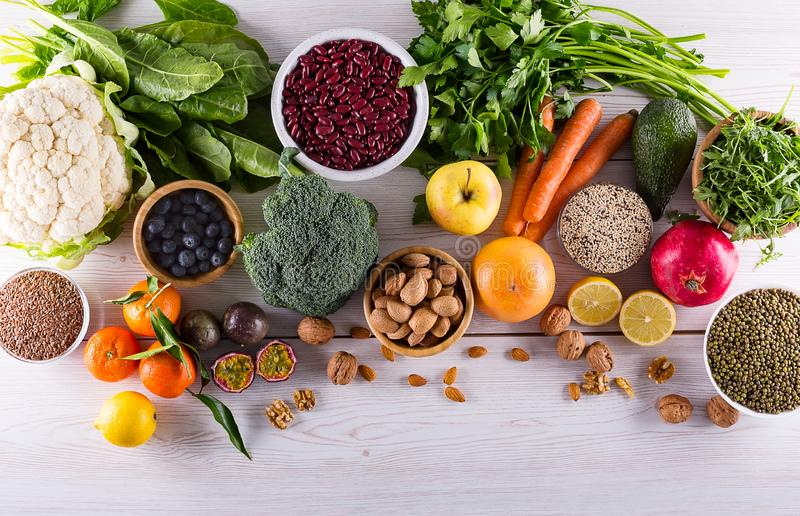 Top view of selected healthy and clean foods. Healthy food clean eating : fruit, vegetable, seeds, superfood, cereals, leaf vegetable on black wood background stock image