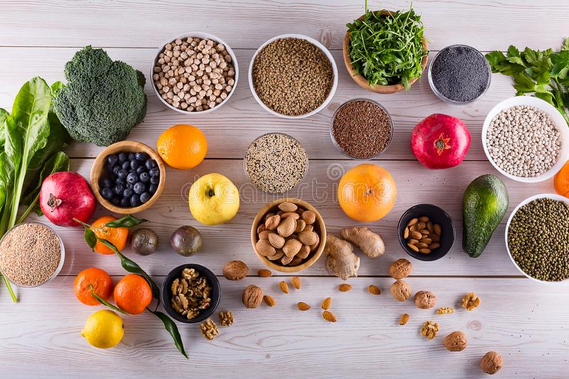 Top view of selected healthy and clean foods. Healthy food clean eating : fruit, vegetable, seeds, superfood, cereals, leaf vegetable on black wood background royalty free stock photography