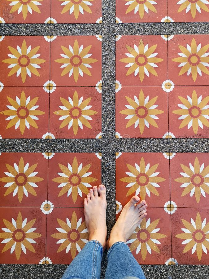 Top View Selfie of Bare Feet on Flower Tile Floor. Woman Wear Blue Jeans and Feet on Art Copy Space stock images