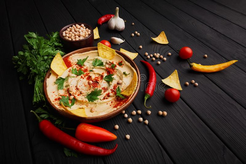 Top view of served hummus. Healthy hummus dip with vegetables on a wooden background. Middle eastern restaurant concept. royalty free stock photo