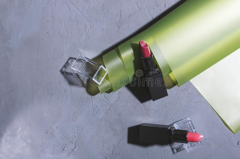 Top view of set of lipsticks adn wrapping material on the grey surface.Presentation of cosmetic products stock photos
