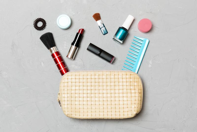 Top view of set of make up and skin care products spilling out of cosmetics bag on cement background. Beauty concept.  stock image