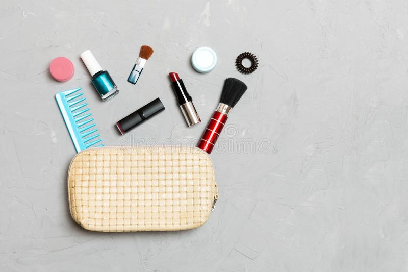 Top view of set of make up and skin care products spilling out of cosmetics bag on cement background. Beauty concept royalty free stock photography