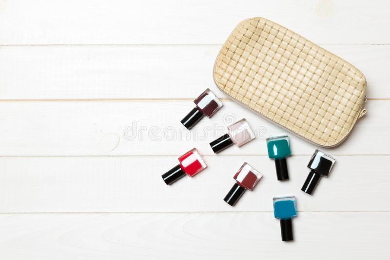 Top view of the set of nail polishes and bright gel varnishes fallen out of cosmetics bag with copy space on wooden background. stock photo