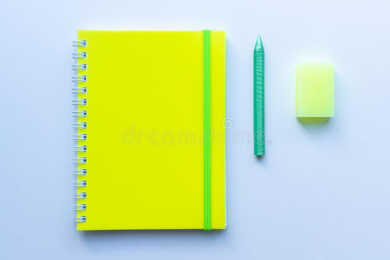 Top view of the set of stationery: yellow notepad with green stripe, green crayon pencil and yellow eraser on white background. Co stock photo
