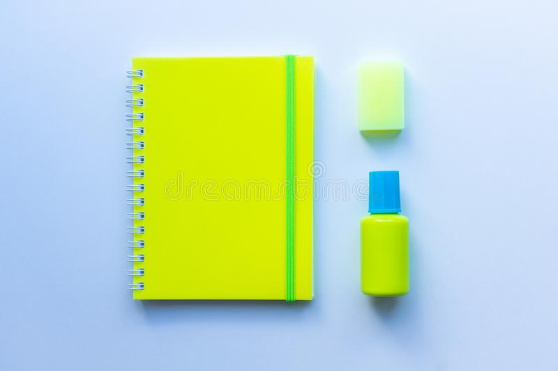 Top view of the set of stationery: yellow notepad with green stripe, yellow eraser and blue and yellow masking fluid on white back royalty free stock photography